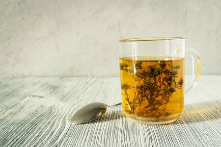 Herbal tea with a very useful and medicinal thyme plant on a gray wooden background