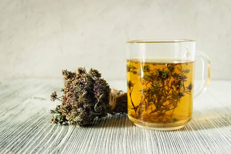 Herbal tea with a very useful thyme plant and bundled dried thyme on a gray wooden background