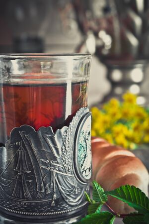 A glass of tea with thyme in a Cup holder on a cloth napkin with bagels on the background of a samovar close-up