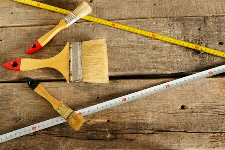 Paint brushes and tape measure tape on the background of old wooden boards Stok Fotoğraf