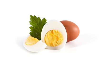 One egg in a brown shell, half and a quarter of a boiled egg with green leaves of parsley on a white background