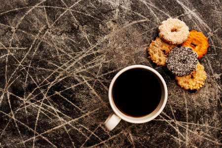 Coffee in a white cup and cookies of different colors and tastes on a dark scratched background