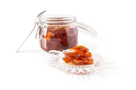 Jam from apple slices in a glass jar close-up and a socket with jam isolated on a white background