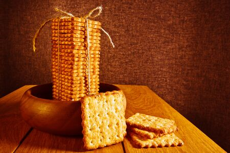 A stack of cookies cracker tied with a rope is in a wooden plate that stands on a wooden tabletop, next to a plate of several pieces of cookies