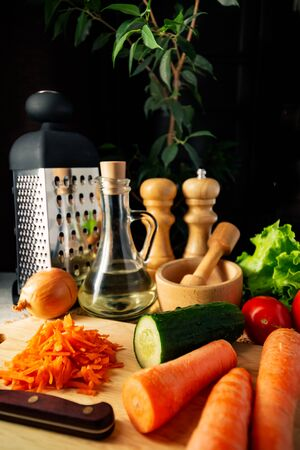 Kitchen still life, grater and jug with vegetable oil, grated and whole carrots on a cutting board and other vegetables