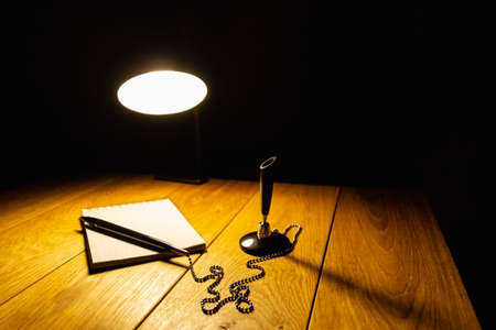 Notepad and pen on a wooden table in the light of a table lamp