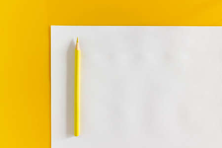 Yellow pencil and blank sheet of white paper on a yellow background Фото со стока - 152367675
