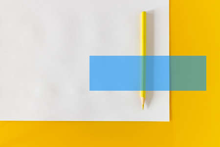 Yellow pencil and blank sheet of white paper on a yellow background