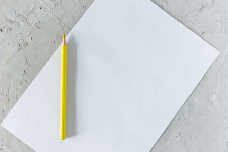 Yellow pencil and blank sheet of white paper on gray concrete background