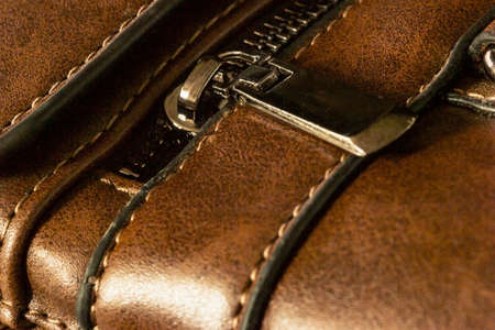 Close-up of a zip fastener with a lock on a leather product