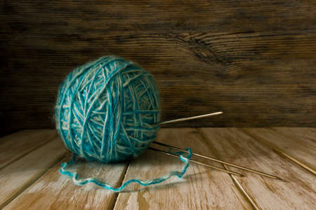 Ball of two-tone wool and knitting needles on old painted wooden background Фото со стока