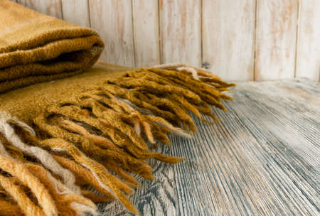 A fragment of a warm classic light brown plaid with a fringe on a wooden surface Фото со стока
