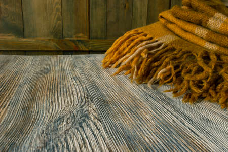 A fragment of a warm classic light brown plaid with a fringe on a wooden surface Фото со стока - 164364793