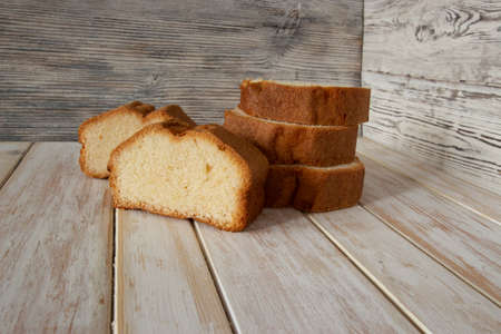 Slices of delicious sponge cake on wooden background