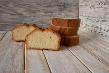 Slices of delicious sponge cake on wooden background Фото со стока - 165896029