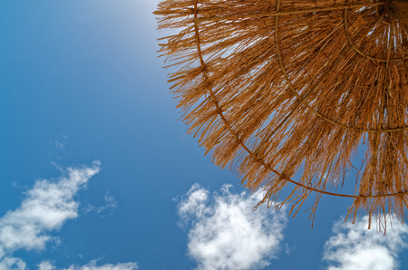 View from bottom on the blue sky and straw parasol at the sandy beach on Sal in Cape Verde.