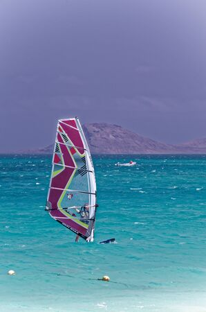windsurf: Isolated on white background. Stock photography Beautiful young woman with a laptop. Isolated on white background. Recreational watersports during idyllic summer vacation. Island of Sal, Cape Verde