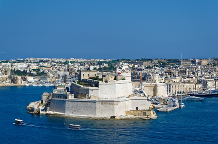 View to the Ancient limestone walls and towers of Fort St Angelo from Upper Barrakka Gardens, view across the Grand Harbor, Valletta, Malta.