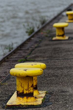 Yellow bollards on the quay. Hamburg Blankenese, Germany Stock Photo