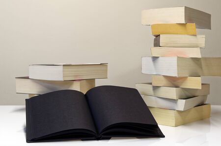 Black open book in foreground of two piles of books on the white table and light grey background