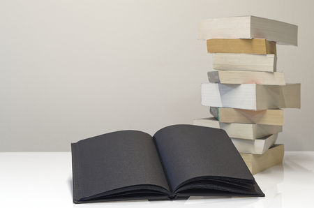 Black open book in foreground of pile of books on the white table and light grey background