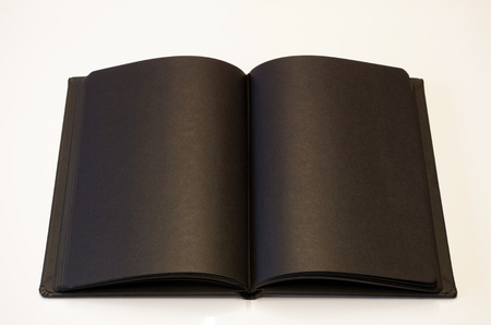 Black book lying open on white background Stock Photo
