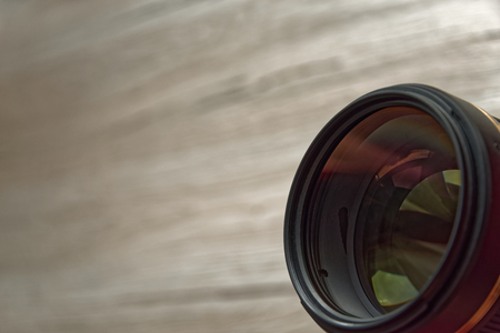 Camera lens on the bottom right and wooden background 写真素材