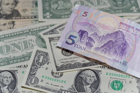 Banknote of five Chinese yuan against background of american dollars