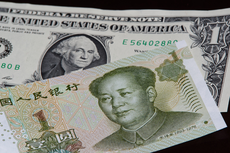 One chinese yuan banknote is above one american dollar on black background