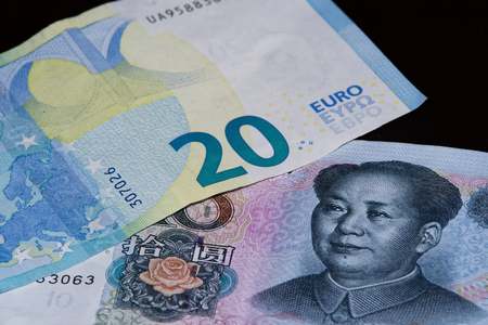 Twenty euro banknote is above ten chinese yuan on black background 스톡 콘텐츠