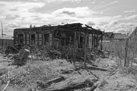 Old burnt house against cloudy sky as black and white image. Komsomolsk-on-Amure, Russia Stock Photo