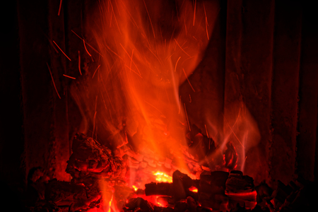 Red flames from burning wood in a fireplace at home Stock Photo