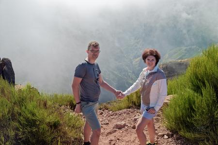 Couple standing on the edge of ravine and looks towards camera. Pico do Arieiro on the Portuguese island of Madeira. Zdjęcie Seryjne