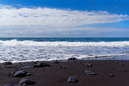 Panoramic view on a black sand beach against blue sky. Praia Formosa beach in Funchal on Portuguese island of Madeira