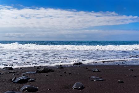 Panoramiczny widok na czarną, piaszczystą plażę na tle błękitnego nieba. Plaża Praia Formosa w Funchal na portugalskiej wyspie Madera