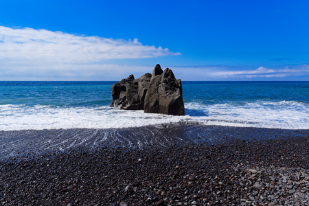 Panoramic view at the rock formation on a beach against blue sky. Praia Formosa beach in Funchal on Portuguese island of Madeira Banco de Imagens