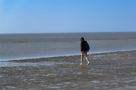 Woman in a black coat and with bare legs is walking on a beach. Sankt Peter-Ording in northern Germany