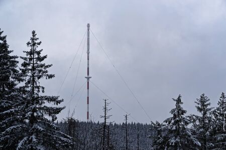 Communication antenna in a winter forest. Harz Mountains National Park, Germany