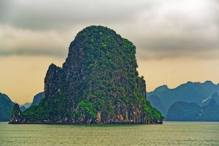 Green rocky islands in HaLong bay at sunset. Ha Long bay is UNESCO World Heritage Site and very popular travel destination in Vietnam