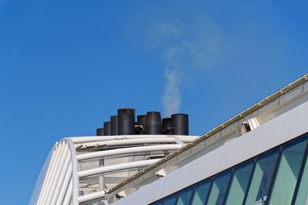 Gray-white smoke from the funnel of a cruise ship against clear blue sky Stock fotó