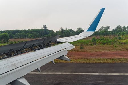 Airplane wing in working order at braking on the runway. View from porthole.