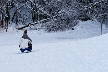 Young woman sledding on a sled by a toboggan run. Torfhaus resort in Harz mountains national park, Germany