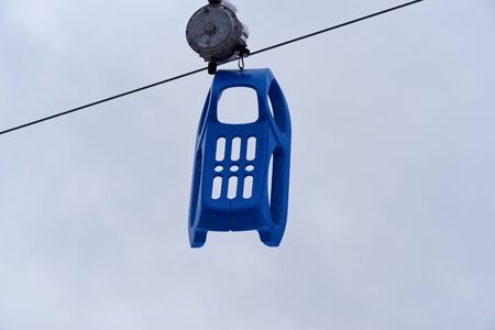 Blue plastic sled is hanging on a toboggan lift. Torfhaus in Harz mountains national park, Germany Standard-Bild