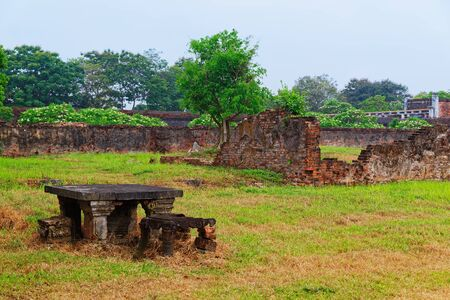 Old stone table against destroyed brick wall on the inner courtyard of Purple Forbidden city (Imperial city) in Hue, Vietnam. The inner yard of Forbidden city was completely destroyed during the war.