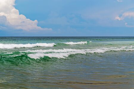Waves on sandy beach against blue sky. Da Nang, Vietnam