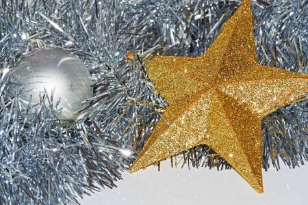 Christmas decoration on white background, silver colored bauble and golden star lying in a tinsel 版權商用圖片