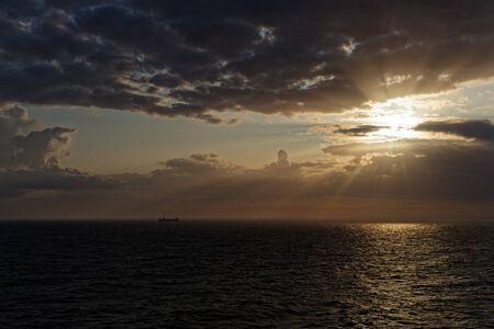 Sun beams through clouds over the sea. Beautiful sunset scene.