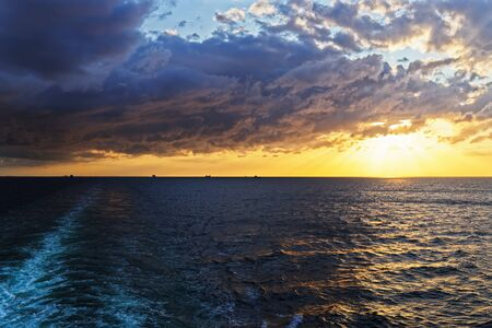 Colorful cloudy sky above sea ans wake from cruise ship at sunset 版權商用圖片