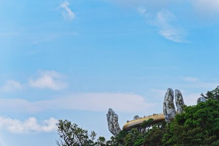 Low angle view of The Golden Bridge lifted by two giant hands against blue sky. Ba Na Hills, Vietnam Standard-Bild