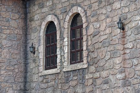 Looking at a building wall and two windows in medieval style